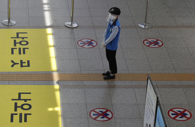 An employee wearing a face mask and face shield stands to guide passengers to maintain a one-way walk flow as a precaution against the coronavirus at the Seoul Railway Station in Seoul, South Korea, Thursday, September 10, 2020. (Photo by Lee Jin-man/AP Photo)