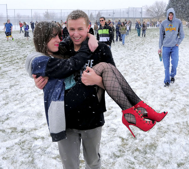 Talon Richards carries Aubree Owens across a field as snow falls after Mountain Crest High School was evacuated because of smoke in the building, Thursday, November 13, 2014, in Hyrum, Utah. (Photo by Eli Lucero/AP Photo/The Herald Journal)