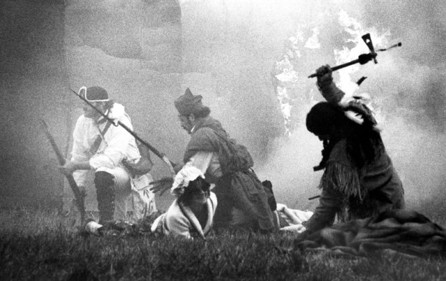Amid smoke from musket volleys and burning buildings, Seneca Indians and Tories press the attack in a re-enactment of the 200th anniversary of the Cherry Valley massacre of 1778 in Cherry Valley, New York, October 16, 1978. The original raid on this Mohawk Valley village occurred in November but local officials moved the re-enactment up in hopes of favorable weather. They got heavy rain and snow. (Photo by AP Photo)