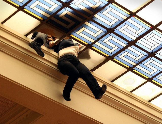 An employee of the Greek Parliament hangs after falling through the glass roof over the Greek Parliament Hall, in her efforts to prevent rain water from entering the building, in Athens, Greece, on February 22. A heavy storm of rain and sleet in the greater Athens region created problems with transportation, flooding streets and interrupting sea transport. (Photo by Pantelis Saitas/EPA)