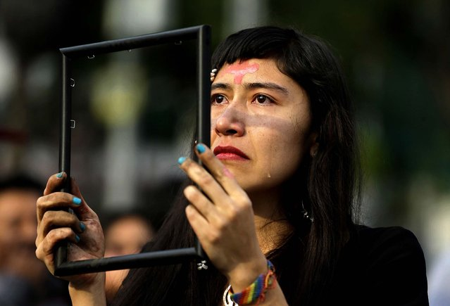 A woman sheds tears as she holds up an empty picture frame during a performance held prior to an International Women's Day march organized by mothers of disappeared daughters, in Ciudad Juarez, Mexico. (Photo by Dario Lopez-Mills/Associated Press)