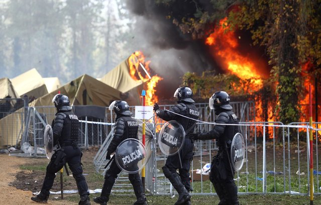 Slovenian policemen walk as a fire sweeps through a migrant camp in Brezice, Slovenia, October 21, 2015. The cause of the fire was not immediately known but many of the camp's tents were destroyed in the blaze. (Photo by Zeljko Lukunic/Reuters/Pixell)