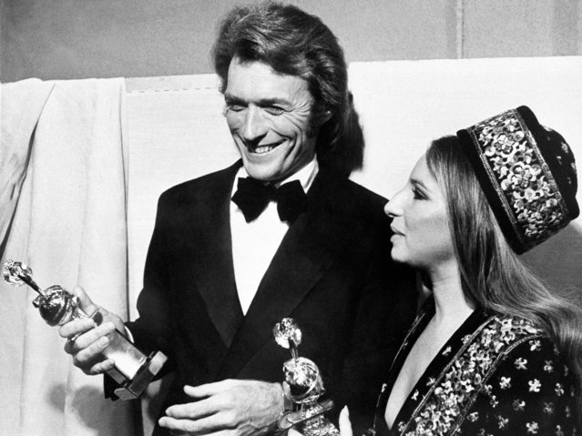 """Actor Clint Eastwood and actress Barbra Streisand admire their Golden Globes after they were presented to them at the Hollywood Foreign Press Association's Golden Globes Awards in Hollywood, California on February 6, 1971. They both won their awards for being named """"World Film Favorites"""". (Photo by Ed Widdis/AP Photo)"""