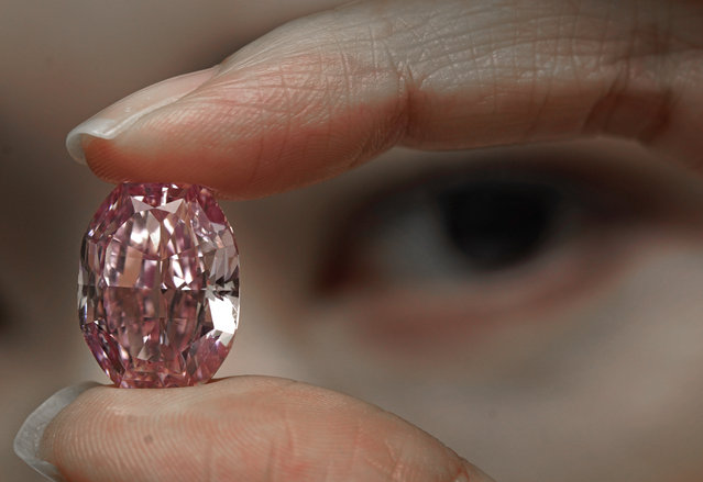 A model displays an ultra-rare 14.83-carat diamond that is one of the largest internally flawless fancy vivid purple-pink gem ever graded by the Gemological Institute of America at a Sotheby's auction room in Hong Kong on Monday, October 12, 2020. The diamond will be offered for sale in Geneva on Nov. 11, 2020. (Photo by Vincent Yu/AP Photo)