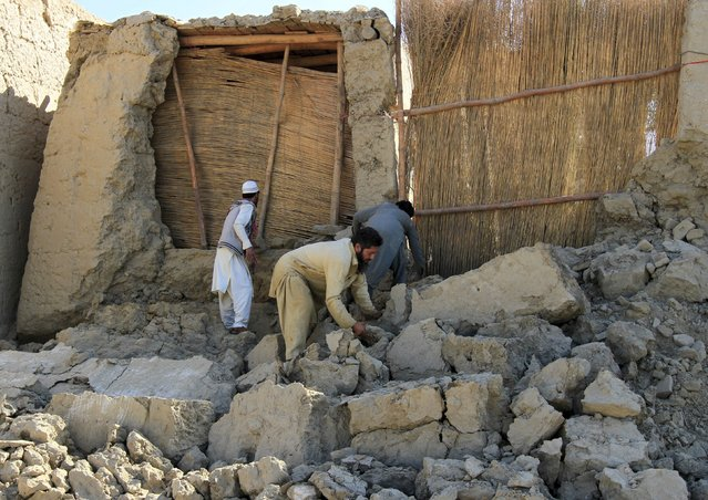 Afghan men clears bricks from a house after it was damaged by an earthquake in Behsud district of Nangarhar province, Afghanistan October 27, 2015. (Photo by Reuters/Parwiz)