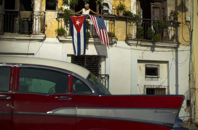 In this  July 20, 2015, file photo, Javier Yanez looks out from his balcony where he hung a U.S., and a Cuban national flag, to celebrate the restored full diplomatic relations between Cuba and the Unites States, in Old Havana. The Cuban government has not announced any big deals with American companies since December 17. (Photo by Ramon Espinosa/AP Photo)