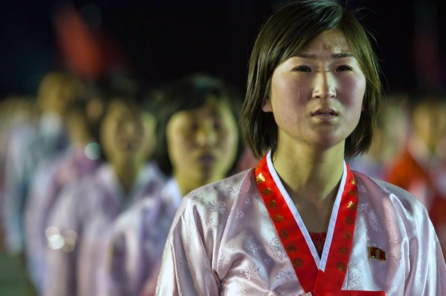 A North Korean woman weeps while singing a song about North Korean leader Kim Jong Un at the end of a mass dance performance in Kim Il Sung Square in Pyongyang, on April 16, 2012. (Photo by David Guttenfelder/AP Photo)