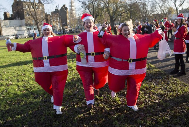 Participants dressed in Santa costumes pose for a photograph during the annual SantaCon event in London December 6, 2014. (Photo by Neil Hall/Reuters)