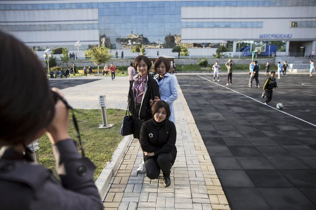Girls take pictures of themselves at a park in front of the Pothonggang Department Store in central Pyongyang October 11, 2015. (Photo by Damir Sagolj/Reuters)