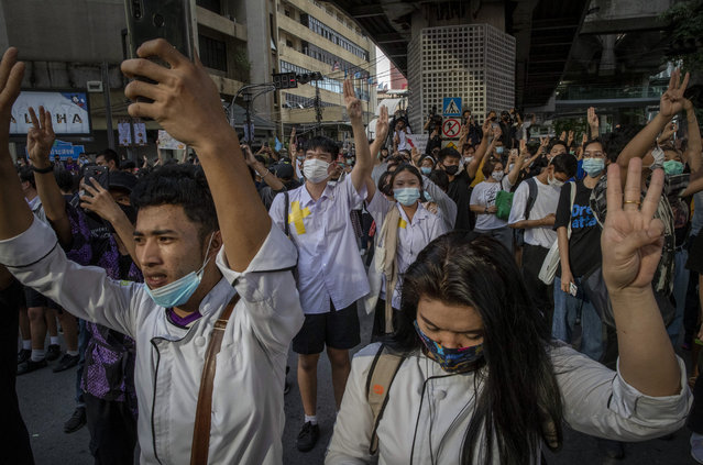 Pro-democracy students, covering their school identification with duct-tapes, flash three-fingered salute during a protest march at the central business district in Bangkok, Thailand, Thursday, October 15, 2020. Thailand's government declared a strict new state of emergency for the capital on Thursday, a day after a student-led protest against the country's traditional establishment saw an extraordinary moment in which demonstrators heckled a royal motorcade. (Photo by Gemunu Amarasinghe/AP Photo)