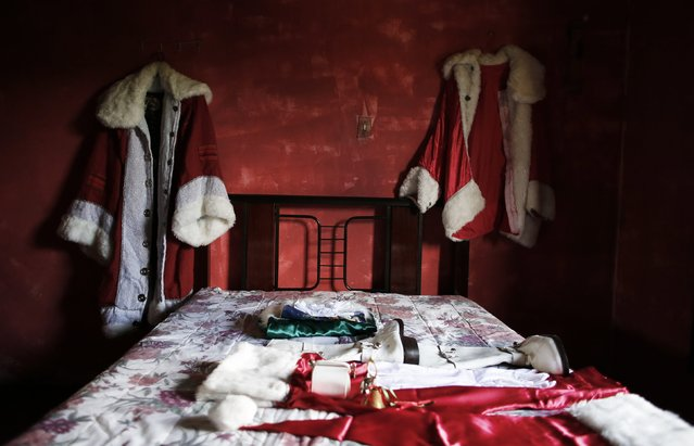 A Santa Claus costume, belonging to Vitor Martins (not pictured), is seen in the bedroom of his house, before a performance with children in Sao Caetano do Sul's town square, near Sao Paulo, December 7, 2014. (Photo by Nacho Doce/Reuters)