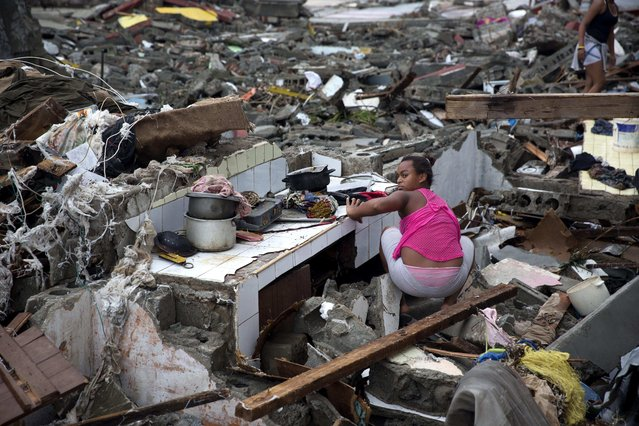 A woman searches amid the rubble of her home destroyed by Hurricane Matthew in Baracoa, Cuba, Wednesday, October 5, 2016. (Photo by Ramon Espinosa/AP Photo)