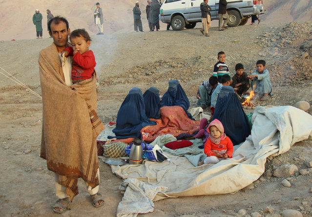 An Afghan family waits for help from the government and aid organizations in Takhar, Afghanistan October 11, 2016, after fleeing their homes in neighboring Kunduz, which has been the scene of fighting between Taliban militants and government troops. (Photo by Nasir Wakif/Reuters)