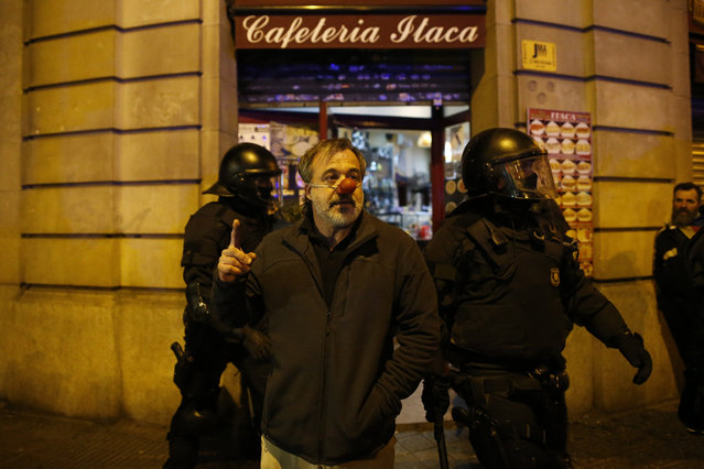 A man with a red plastic clown's nose stands in front of two Catalan Mossos d'Esquadra regional police officers in riot gear during a protest over the detention of deposed leader of Catalonia's pro-independence party Carles Puigdemont in Barcelona, Spain, Sunday, March 25, 2018. Puigdemont was arrested Sunday by German police on an international warrant as he tried to enter the country from Denmark. (Photo by Manu Fernandez/AP Photo)