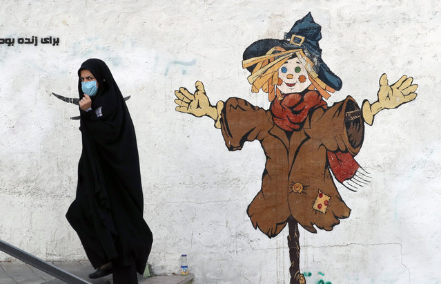 An Iranian woman wearing a face mask walks on a street in Tehran, Iran, 19 October 2020. According to the Iranian Health ministry, Iran reported its highest daily COVID-19 death toll of 337 and 4,251 new infections in past 24 hours as it appears that Iran is in a third wave of COVID-19 outbreak. (Photo by Abedin Taherkenareh/EPA/EFE)