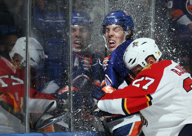 Travis Hamonic #3 of the New York Islanders is hit into the glass by Nick Bjugstad #27 of the Florida Panthers during the first period at the Nassau Veterans Memorial Coliseum on April 1, 2014 in Uniondale, New York. (Photo by Bruce Bennett/Getty Images)