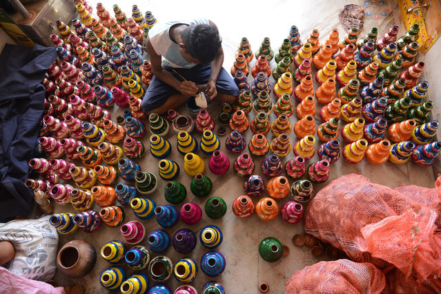 An Indian artist decorates earthenware oil pots or 'diyas' at his workshop on the outskirts of Hyderabad on November 6, 2015, ahead of the Diwali festival of lights.  Diyas, which are lit and placed around the home, are in heavy demand during the festival which marks the victory of good over evil and commemorates Hindu God Lord Rama's victory over Ravana and return to his Kingdom Ayodhya after 14 years of exile. (Photo by Noah Seelam/AFP Photo)