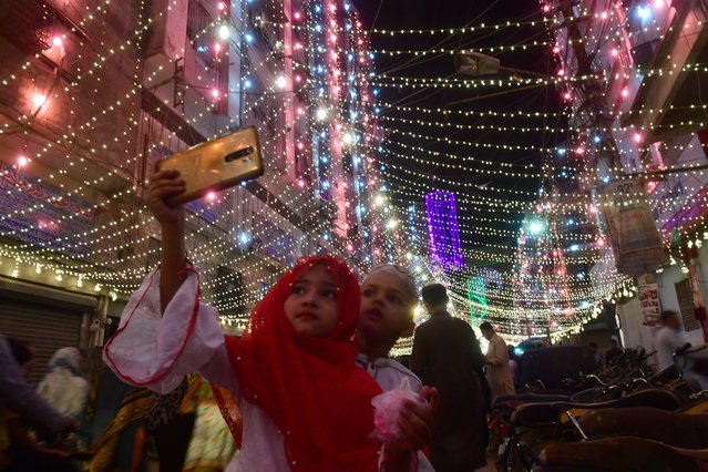 A young girl takes a selfie with her brother in an illuminated street ahead of celebrations for Eid-e-Milad-un-Nabi, the birthday of Prophet Mohammad, in Pakistan port city of Karachi on October 28, 2020. (Photo by Asif Hassan/AFP Photo)
