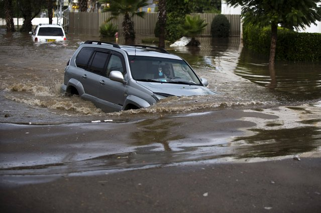A motorist tries to drive a vehicle through a flooded street in the southern city of Ashkelon, Israel, November 9, 2015. (Photo by Amir Cohen/Reuters)