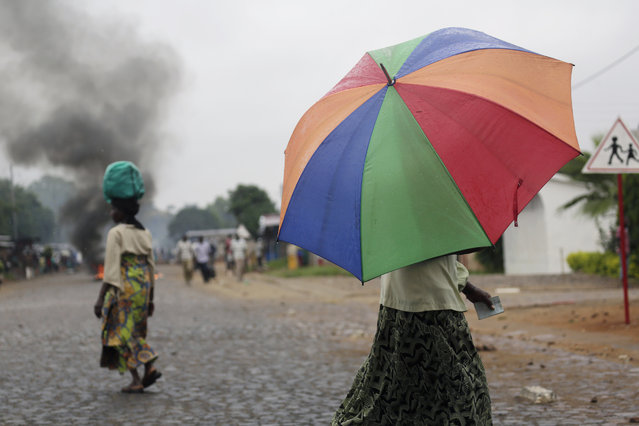 A woman protecting herself from the rain with an umbrella walks near a burning barricade in Bujumbura, Burundi Thursday, April 30, 2015, after the government issued and ordered for all campuses to close down. (Photo by Jerome Delay/AP Photo)
