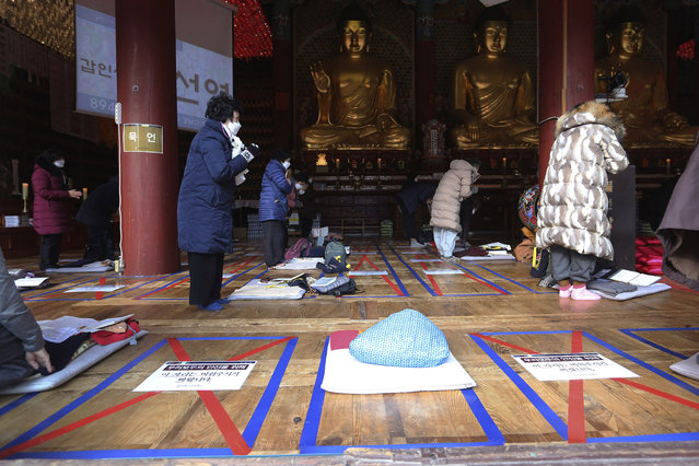 """Social distancing signs are seen on the floor as parents pray during a special service to wish for their children's success in the upcoming college entrance exam on Thursday, Dec. 3, at the Jogye Temple in Seoul, South Korea, Sunday, November 29, 2020. South Korea is shutting down indoor gyms offering intense workout classes and banning year-end parties at hotels in the greater Seoul area to fight the virus. Prime Minister Chung Sye-kyun said Sunday. The signs read: """"Please empty this place"""". (Photo by Ahn Young-joon/AP Photo)"""