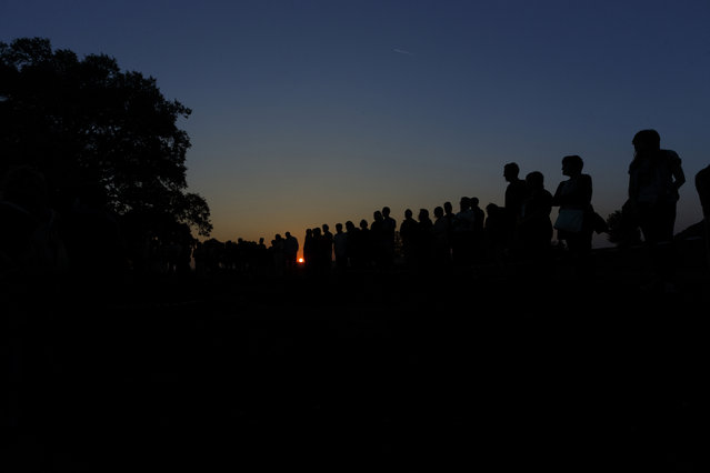 In this photo taken on July 26, 2014, the sun sets as people attend an homage to those killed by their political ideology during and after the Spanish civil war at the site where four mass graves with at least 80 skeletons where found in El Estepar, Spain. (Photo by Daniel Ochoa de Olza/AP Photo)