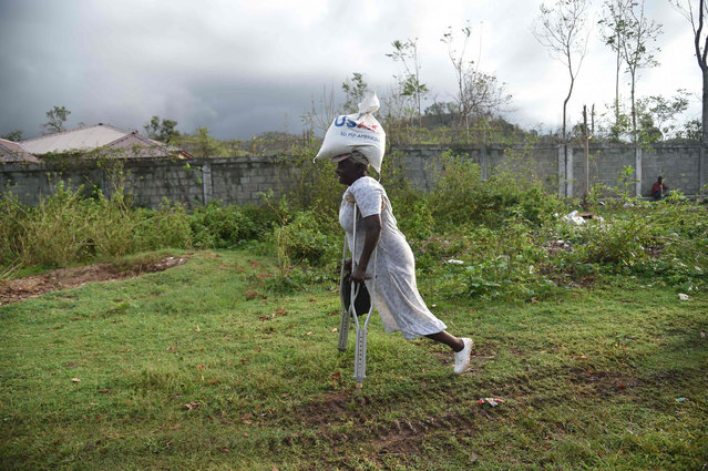 """Sara (66) walks after receiving a food delivery for the World Food Programme in the commune of Maniche, in Les Cayes, in the south west of Haiti, on October 17, 2016. Haiti faces a humanitarian crisis that requires a """"massive response"""" from the international community, the United Nations chief said , with at least 1.4 million people needing emergency aid following last week' s battering by Hurricane Matthew. (Photo by Hector Retamal/AFP Photo)"""