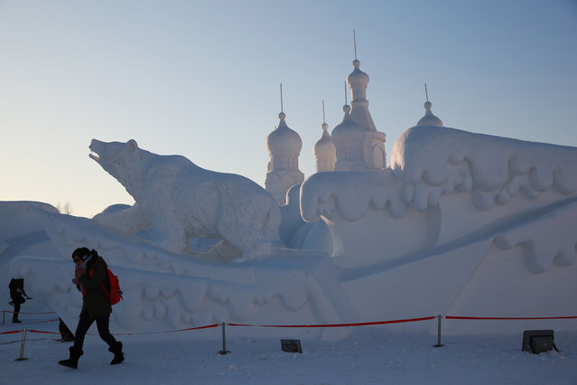 A visitor passes by a Russian-theme snow sculpture in the 16th Harbin Ice and Snow World, which will officially open on January 5 on December 22, 2014 in Harbin, China. (Photo by Feature China/Barcroft Media)