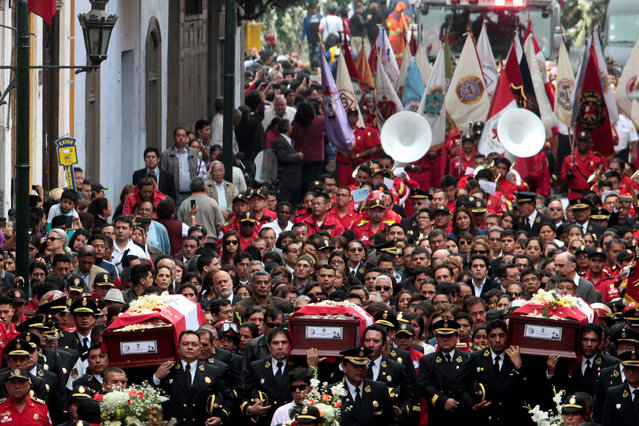 Firefighters, relatives and people attend a mourning ceremony, for the three firefighters killed during a fire at a shoe factory, in Lima, Peru, October 21, 2016. (Photo by Guadalupe Pardo/Reuters)