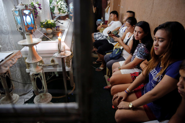 Friends and relatives mourn by the coffin during a wake for Florjohn P. Cruz who was killed in a police drugs buy bust operation in Manila, Philippines late October 20, 2016. (Photo by Damir Sagolj/Reuters)