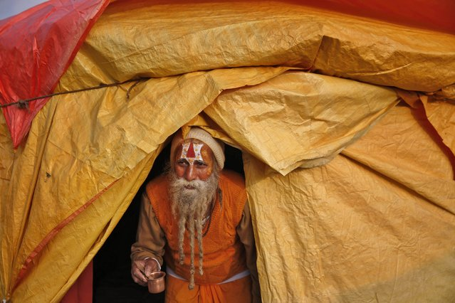"An Indian Hindu Holy man carries a glass as he walks out of his tent to perform a ritual ahead of the annual month long Hindu religious fair ""Magh Mela"", in Allahabad, India, Sunday, January 4, 2015. (Photo by Rajesh Kumar Singh/AP Photo)"