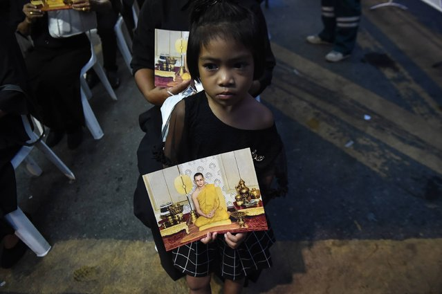 A girl dressed in black holds an image of the late Thai King Bhumibol Adulyadej, while waiting to enter the Grand Palace to pay respects, in Bangkok on October 29, 2016. Thousands of Thais streamed into the gates of Bangkok's Grand Palace on Saturday as the public was granted its first chance to enter the throne hall where the body of late King Bhumibol Adulyadej is lying in state. (Photo by Lillian Suwanrumpha/AFP Photo)