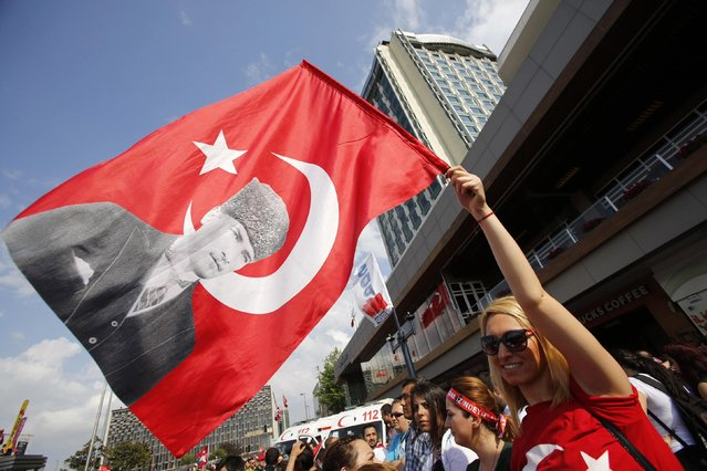 A demonstrator waves a Turkish flag with a portrait of Mustafa Kemal Ataturk during an anti-government protest at Taksim Square in central Istanbul June 2, 2013. Prime Minister Tayyip Erdogan accused Turkey's main secular opposition party on Sunday of stirring a wave of anti-government protests, as tens of thousands regrouped in Istanbul and Ankara after a lull and trouble flared again in the capital. (Photo by Murad Sezer/Reuters)