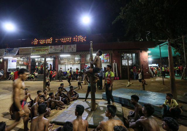 "A student practices during a training session of the Pole Mallakhamba, during the 44th Samartha Summer Sports Coaching Camp organized by Shree Samarth Vyayam Mandir in Mumbai, India, 23 April 2018. Mallakhamba arose in the western state of Maharashtra centuries ago. It was originally practiced by wrestlers and soldiers as a strength training exercise. ""Malla"" means ""wrestler"" and ""khamb"" means ""pole"" in Marathi, though the term is the same in Kannada and Tamil. It is a sport of strength and power, which provides a complete exercise for the entire body in a short period of time. Mallakhamba requires the strength of wrestling and the flexibility of gymnastics and yoga, and practitioners must combine those elements to perform aerial yoga poses while gripping a vertical pole. The pole is made of Seesham (Indian Rosewood) and polished with castor oil to reduce friction and minimize the risk of injury. There are three main variations of Mallakhamba: pole Mallakhamba, hanging Mallakhamba and rope Mallahkhamba. With the pole type, performers do acrobatic feats and pose on a 10-12 foot high wooden pole, fixed into the ground. The pole is 5 to 6 inches in diameter at the bottom and narrows to 1.5-2 inches in diameter at the top. Hanging Mallakhamba involves a swinging pole. The performers display their acrobatic tricks on a short pole, which is suspended by rope or with chains and hooks. The pole hangs 3 to 4 feet above the ground. Rope Mallakhamba replaces the pole with a rope, which the performers hold onto while doing acrobatic maneuvers. The rope is 5.5 meters long and 1-2 centimeters in diameter. (Photo by Divyakant Solanki/EPA/EFE)"