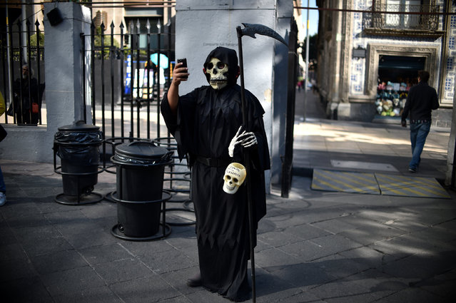 """A man dressed as the """"Death"""" takes a selfie while attending the exhibition and contest of altars organized by the Historic Centre Foundation in the framework of the Day of the Dead, in Mexico City on November 1, 2016. Mexicans who culturally celebrate and revere death begin to honour their deceased loved ones in the three-day Day of the Dead festivities. (Photo by Yuri Cortez/AFP Photo)"""