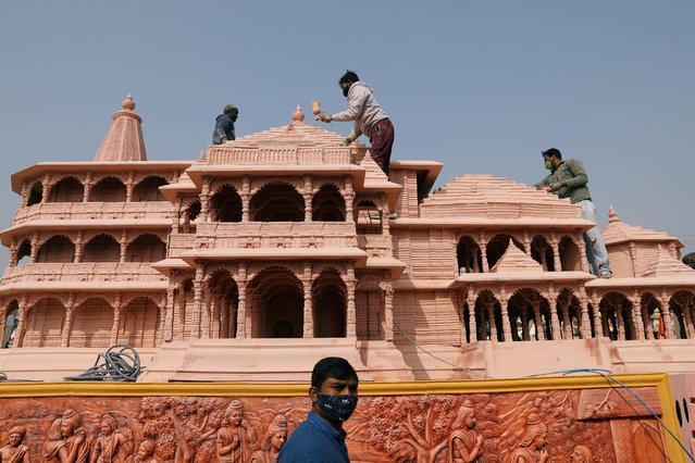 Workers give finishing touches to the model of the proposed Ram temple that Hindu groups want to build at a religious site in Ayodhya, on a tableau during a media preview of tableaux participating in the Republic Day parade in New Delhi, India on January 22, 2021. (Photo by Anushree Fadnavis/Reuters)