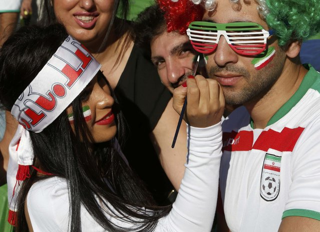 An Iran supporter applies face paint to another fan before the Asian Cup Group C soccer match betweeen Iran and Bahrain at the Rectangular stadium in Melbourne January 11, 2015. (Photo by Brandon Malone/Reuters)
