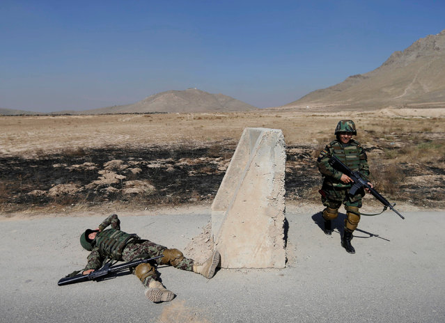 Afghan soldier Tamana, 19 (L), and commander for female soldiers Lieutenant Colonel Cobra Tanha, 45 (R), simulate an injury during a training exercise at the Kabul Military Training Centre (KMTC) in Kabul, Afghanistan October 26, 2016. (Photo by Mohammad Ismail/Reuters)