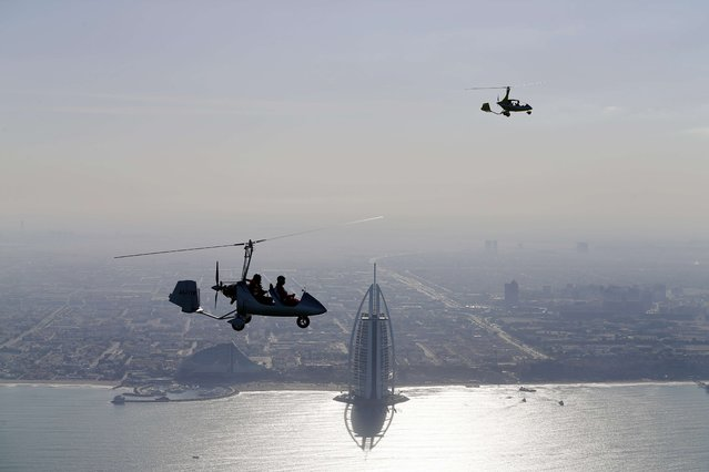 Gyrocopters fly over the capital of the United Arab Emirates, Dubai, during the World Air Games 2015, on December 9, 2015. (Photo by Karim Sahib/AFP Photo)