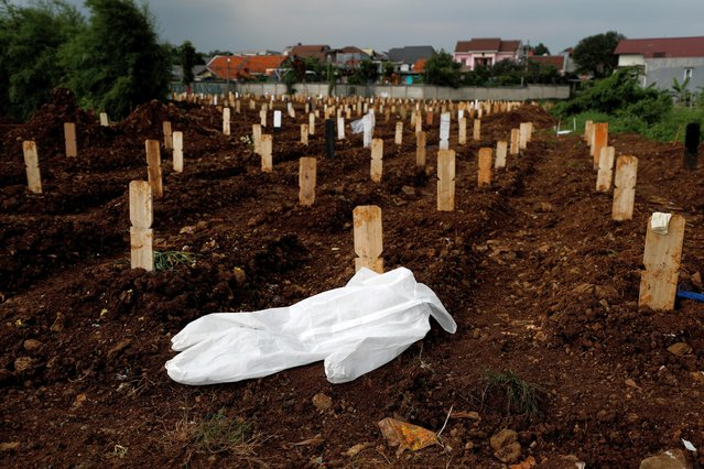 A protective suit lies on the ground at a burial area provided by the government for the victims of the coronavirus disease (COVID-19), at the Srengseng Sawah cemetery complex, in Jakarta, Indonesia, January 25, 2021. (Photo by Willy Kurniawan/Reuters)