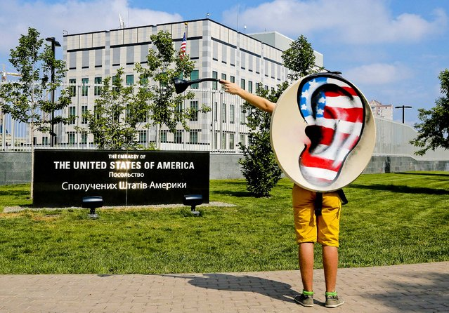 An activist of Ukraine's Internet party gestures as he demands the American authorities to stop their pursuit of National Security Agency leaker Edward Snowden during a protest near the US Embassy in Kiev, Ukraine, on June 27, 2013. (Photo by Efrem Lukatsky/Associated Press)