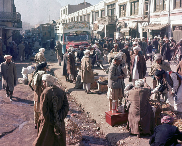 Men stroll past roadside vendors as a painted truck makes its way through the busy street in Kabul, Afghanistan, November, 1961. (Photo by Henry S. Bradsher/AP Photo via The Atlantic)