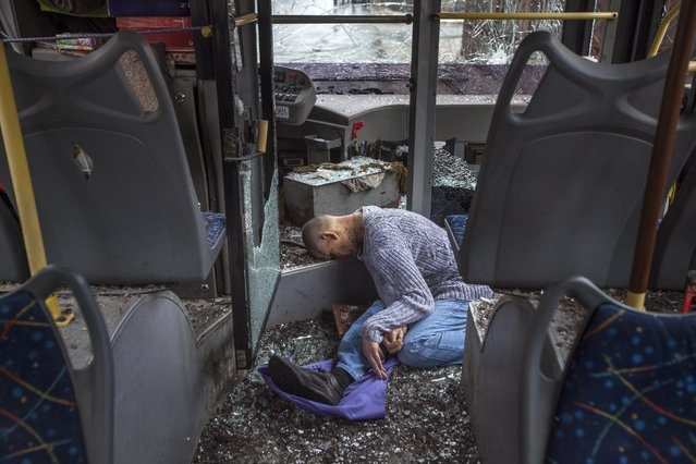 A passenger killed when a trolley bus was damaged by a mortar shell is seen inside the bus in Donetsk, eastern Ukraine, Thursday, January 22, 2015. A new peace initiative for Ukraine began taking shape as mortar shells rained down Thursday on the center of the main rebel-held city in the east, killing at least 13 people at a bus stop. (Photo by Igor Ivanov/AP Photo)