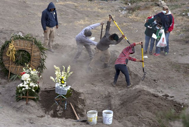 Workers bury 86-year-old Gabina Salgado Husca, who died of complications related to the new coronavirus, in the Valle de Chalco municipal cemetery on the outskirts of Mexico City, Wednesday, November 18, 2020. (Photo by Marco Ugarte/AP Photo)