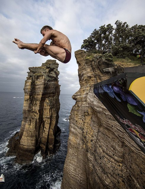 Mat Cowen of the UK dives from the 27 metrer platform during the second competition day of the third stop of the Red Bull Cliff Diving World Series, at Islet Vila Franca do Campo, Azores, Portugal, on June 29, 2013. (Photo by Dean Treml/Red Bull via Getty Images)