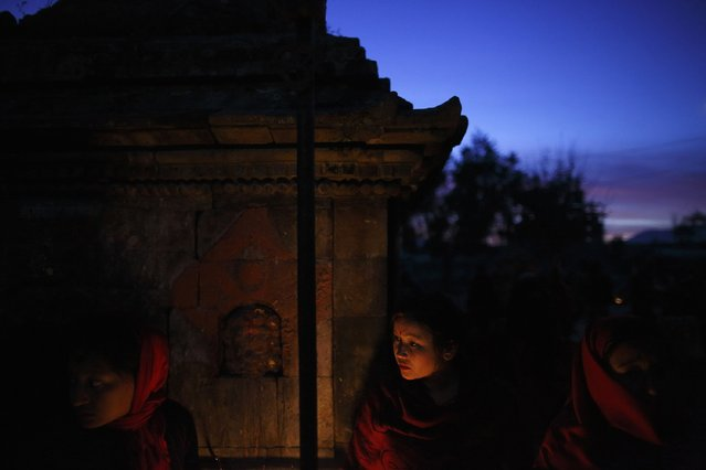 A devotee stands near the fire to keep herself warm in the early morning during the Swasthani Bratakatha festival in Panauti near Kathmandu January 24, 2015. (Photo by Navesh Chitrakar/Reuters)