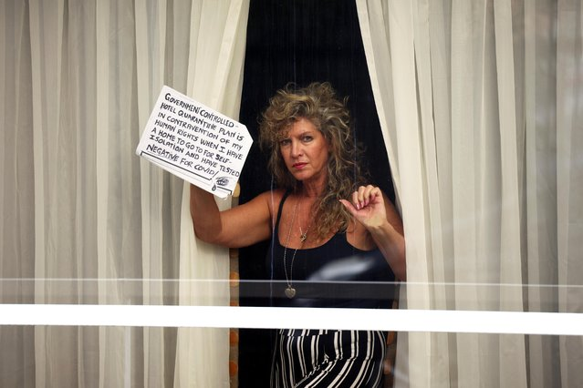 "A woman holds a sign at a window of the Radisson Blu Hotel at Heathrow Airport, as Britain introduces a hotel quarantine programme for arrivals from a ""red list"" of 30 countries due to the coronavirus pandemic, in London, Britain, February 25, 2021. Britain says the measures are needed to protect its COVID-19 vaccination program and guard against new coronavirus variants. (Photo by Henry Nicholls/Reuters)"