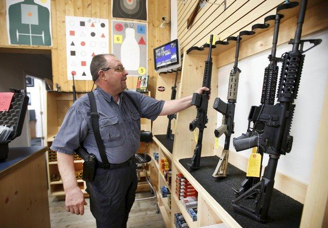 David Warren returns an assault rifle to the display at the Ringmasters of Utah gun range and store, in Springville, Utah on December 18, 2015. (Photo by George Frey/Reuters)