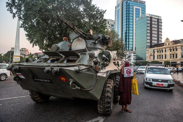 A Buddhist monk holding a sign stands next to an armored vehicle during a protest against the military coup, in Yangon, Myanmar on February 14, 2021. (Photo by Reuters/Stringer)