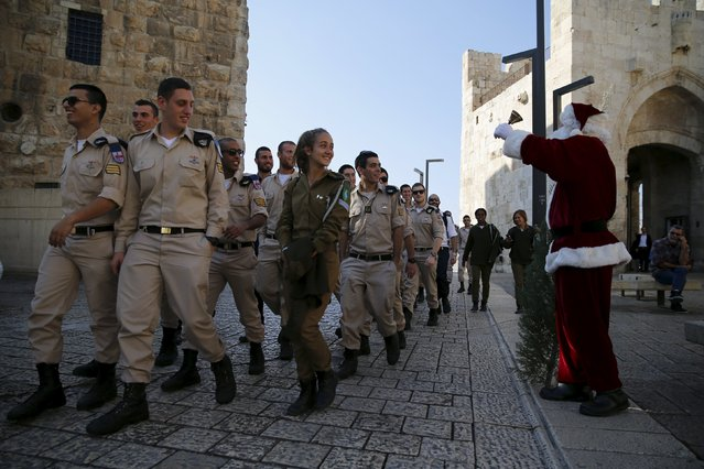 Israeli soldiers look at Israeli-Arab Issa Kassissieh as he wears a Santa Claus costume during an annual Christmas tree distribution by the Jerusalem municipality in Jerusalem's Old City December 21, 2015. (Photo by Ammar Awad/Reuters)